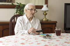 Old woman at the table with remote control for the TV. The old woman turns on the TV remote control sitting at the table. The old woman in glasses sitting at Royalty Free Stock Photo