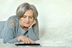 Old woman with tablet pc. Old woman lying in bed with tablet pc Stock Photos