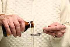 Old woman takes syrup Stock Photos