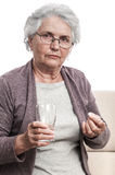 Old woman taking drugs Royalty Free Stock Photos