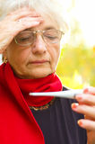 Old woman taking her temperature Stock Photography