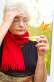 Old woman taking her temperature Stock Images