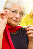 Old woman taking her temperature Royalty Free Stock Image
