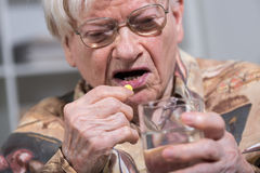Old woman taking medication Stock Photography