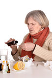 Old woman taking medication. Portrait of an elderly sick woman taking medication over a white background stock image