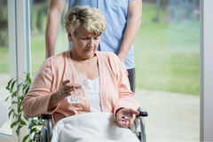 Old woman taking pills Stock Photography