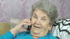 Old woman talking with daughter on mobile phone stock video footage