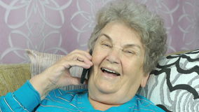 Old woman talking with daughter on mobile phone stock footage