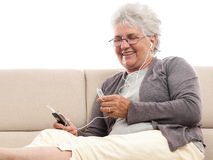 Old woman talking earphones on cellphone Royalty Free Stock Images
