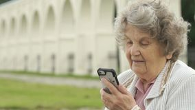 Old woman talking with a friend using a smartphone stock footage