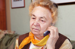 Old woman is talking by a mobile phone Royalty Free Stock Image