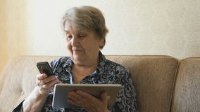 Old woman talking on a mobile phone. That holds digital tablet, sitting on a beige sofa stock video