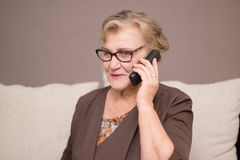 Old woman talking on the phone. Old woman with glasses   talking on the phone Stock Image