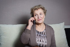 Old woman talking on the phone. Old woman talking on the house phone Stock Photography