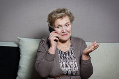 Old woman talking on the phone. Old woman talking on the house phone Stock Image