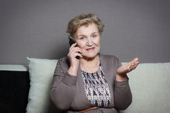 Old woman talking on the phone. Old woman talking on the house phone Royalty Free Stock Images
