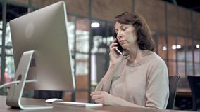 Old Woman Talking on Phone at Work. The Old Woman Talking on Phone at Work stock video footage
