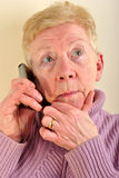 old woman is talking on a telephone Stock Photography