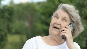 Old woman talking using a mobile phone outdoors. Mature old woman sitting at the green park dressed in a white t-shirt talking with relatives using a silver stock video footage
