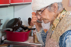 Old woman at tasting on the eat Royalty Free Stock Photography