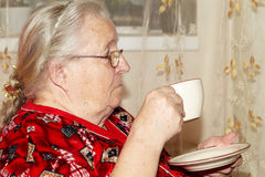 Old woman and tea Stock Images