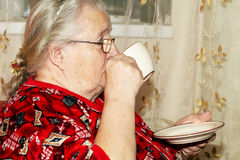 Old woman and tea Royalty Free Stock Image