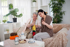 Old woman teaching young woman knitting stock image
