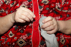 Old woman to sew over a tear. Darning Stock Images