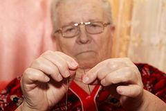 Old woman to thread a needle Stock Image