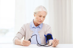 Old woman with tonometer checking blood pressure. Medicine, age, health care and people concept - senior woman with tonometer checking blood pressure level at royalty free stock images