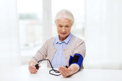 Old woman with tonometer checking blood pressure Royalty Free Stock Photos