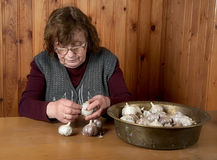 The old woman touches garlic Royalty Free Stock Images