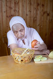 The old woman touches onions sitting Royalty Free Stock Photo