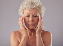 Old woman touching her face. Portrait of old woman touching her face against grey background. Naked senior female pampering her face skin Stock Image