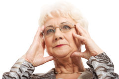 An old woman touching her face/temples. Stock Image