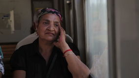 Old woman traveling by train. Old Gypsy woman traveling by train, sitting thoughtful and looking through window stock footage