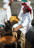 Old woman treats corn pistons. An old woman is treating corn pistons by old fashioned way, 100% Zagorje fair, Zagreb, Croatia, Europe Stock Photography