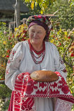 The old woman in Ukrainian national costume presents guests with bread in salt Royalty Free Stock Photo