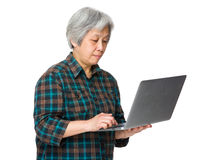 Old woman use of laptop Stock Images