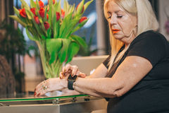 Old woman use smartwatch at home. Old woman touch smartwatch at home Royalty Free Stock Photography