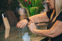 Old woman use smartwatch at home. Old woman touch smartwatch at home Stock Photography