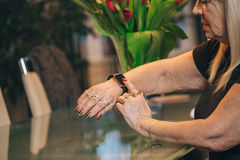 Old woman use smartwatch at home. Old woman touch smartwatch at home Stock Photos