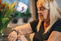 Old woman use smartwatch at home. Old woman touch smartwatch at home Royalty Free Stock Photos
