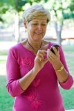 Old woman using cellphone. A old senior woman is dialing on a cellphone Stock Photography