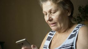 Old woman using new smartphone. Smiling senior woman using new smartphone. Types messege stock footage