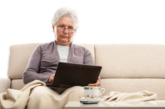 Old woman using tablet with keyboard dock at home Royalty Free Stock Photos