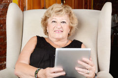 Old woman using tablet. Stock Photo