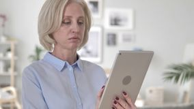 Old Woman Using Tablet at Workplace stock video