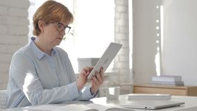 Old Woman Using Tablet at Workplace. 4k high quality stock footage