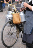 Old woman with very old bicycle and milk cans. Elderly woman with very old bicycle and aluminium milk cans stock photography